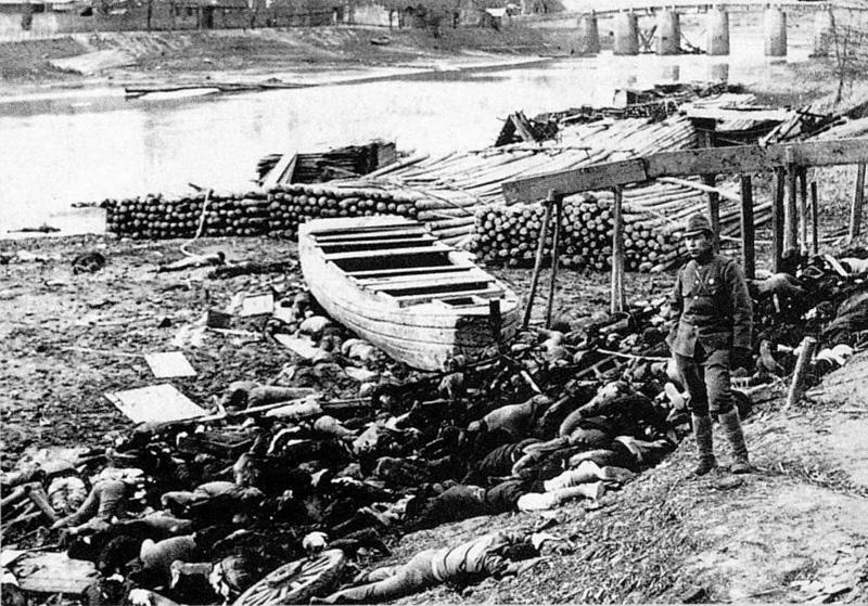 جثث لضحايا من مذبحة نانجنغ على شاطئ نهر تشينهواي يقف بجانبها جندي ياباني.