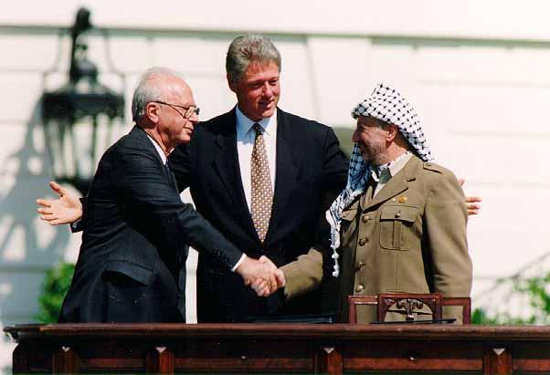 بيل كليتنتون بين عرفات ورابين خلال التوقيع على الاتفاقية